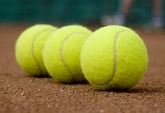 Three tennis-ball. Three yellow tennis balls on a read court, right end ball in focus Stock Image