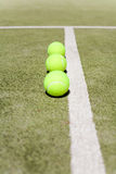 Three tennis balls. And white line Royalty Free Stock Photography