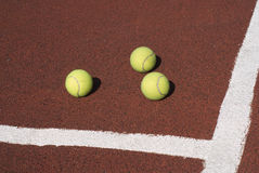 Three tennis balls on brown synthetic court Stock Photography
