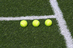 Three tennis balls on green court Stock Image