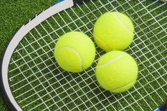 Three tennis balls lie on a tennis racket strings. over green la Royalty Free Stock Images
