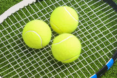 Three tennis balls lie on a tennis racket strings. over green la. Wn surface. tennis concept.horizontal image stock image