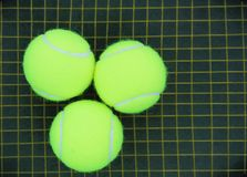 Three tennis balls on a racket strings Stock Photography