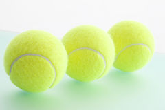 Three Tennis balls in a row, close-up Stock Photography