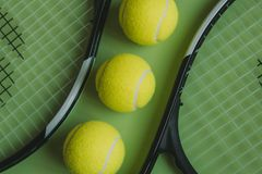 Three tennis balls and two tennis rackets on green background. Top view of tennis conceptual objects set on green color surface Stock Image