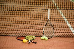 Three tennis rackets and balls on the indoor court stock image