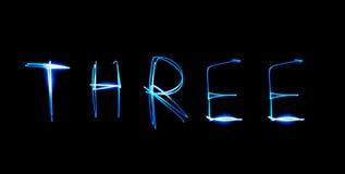 Three - text. Painting light luminescent inscription word Royalty Free Stock Photography