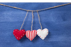 Three textile hearts over wooden wall Royalty Free Stock Photography