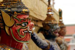 Three Thai devils protecting the temple entrance royalty free stock photography