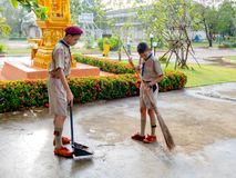 Thai young students in scout uniform help together sweeping the cement floor in their school every morning. Hua Hin, Thailand