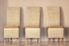 Three thatch chairs. Against rustic wall. Shot in Lesotho stock photography