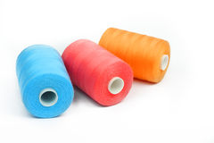 Three thread spools red orange and blue Royalty Free Stock Photos