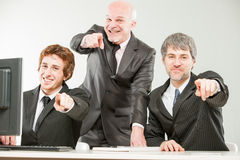 Three thrilled businessmen pointing out to you Royalty Free Stock Image