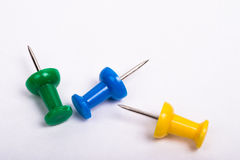Three thumbtacks on a white background. Three thumbtacks, one green, one yellow and one blue on a white background Stock Images