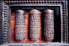 Three Tibetan Prayer Wheels carved with symbols - vintage effect. Stock Images