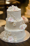 Three tier wedding cake with cream roses and decorations. 3-tier wedding cake in cream color with slightly rose tinted roses in front of a cake store Royalty Free Stock Photography