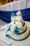Three tiered blue and white wedding cake with confectionery roses. And funny figures Royalty Free Stock Photos