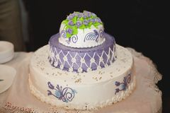 Three-tiered purple wedding cake with green roses royalty free stock photo