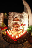 Three tiered wedding cake. Iced decorated  three tiered wedding cake placed on a table surrounded by burning candles Royalty Free Stock Photos