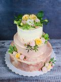 Three-tiered wedding ombre cake decorated with roses and greener Royalty Free Stock Photos