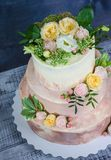 Three-tiered wedding ombre cake decorated with roses and greener Stock Photos