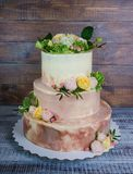 Three-tiered wedding ombre cake decorated with roses and greener Stock Image