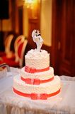 Three-tiered white wedding cake with red ribbons Stock Photo