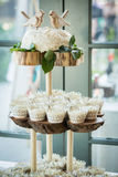 A three tiered wooden display with cupcakes Stock Photos