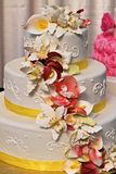 Three Tiers. Three-tiered wedding cake with yellow ribbon and a spray of pastel orchids Royalty Free Stock Image