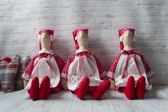 Three tilde dolls in red dresses, and white aprons, and red kalpaks sit on a light background. Interior dolls. There is a place. For text. The concept of royalty free stock photos