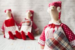Three tilde dolls in red dresses, and white aprons, and red kalpaks sit on a light background. Interior dolls. There is a place stock image