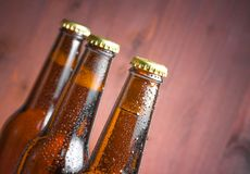 Three tilted bottles of fresh beer with drops Stock Photos