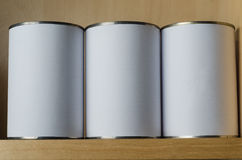 Three Tin Cans On Shelf with Blank White Labels Royalty Free Stock Image
