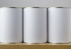 Three Tin Cans with White Labels. Conceptual image of three tin cans with blank white paper labels on a shelf, copy space on labels allows inclusion of Royalty Free Stock Images