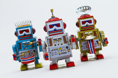 Three Tin Toy Robots. A marching band of 3 tin toy robots in gold, silver and blue Stock Photos