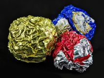 Three tinfoil balls. Three balls colored red, silver, blue and gold made from crumpled tinfoil stock photo