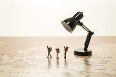Three tiny human models walk on world map with lamp Stock Photos