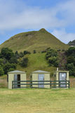 Three tiny Public Bathrooms. Three tiny green public bathrooms under grass covered hillock stock photo