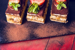Three tiramisu cake on black slate and red wooden Royalty Free Stock Images