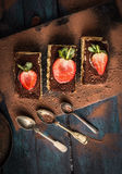 Three tiramisu cake with strawberries and spoons on dark blue wooden Royalty Free Stock Image