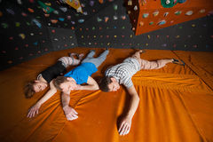 Three tired climbers on the mat near rock wall indoors Royalty Free Stock Image