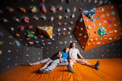 Three tired climbers on the mat near rock wall indoors Stock Image