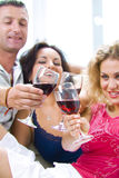 Three and toast. Portrait of young happy attractive people having some wine Royalty Free Stock Image