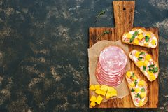 Three toasts with ham, cream cheese and mango on a cutting board, rustic dark background. Top view, copy space. Royalty Free Stock Images