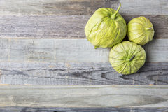 Three Tomatillos on Wooden Table Royalty Free Stock Images