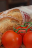 Three tomatoes and a crusty loaf Stock Photos