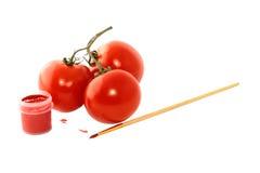 Three tomatoes isolated on white background. Three tomatoes red paint and a brush on a white background Royalty Free Stock Image