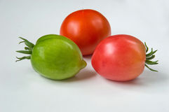 Three tomatoes on a light background. The red and green. Vegetables. Still life. Three tomatoes on a light background. The red and green. Vegetables royalty free stock image