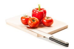 Three tomatoes, one red pepper, knife and wooden board Royalty Free Stock Images