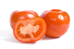 Three tomatoes one of them sliced. Three tomatoes, one of them sliced with drops of water, isolated on white background stock photo